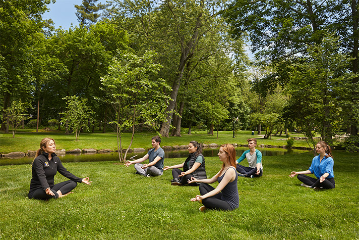 Class Meditating Outside in the Grass | Newport Healthcare